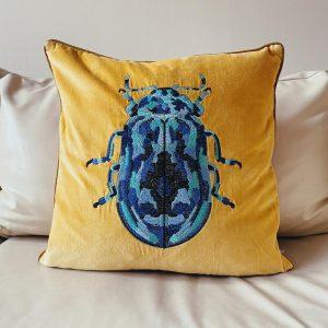 Blue beetle on mustard yellow cushion